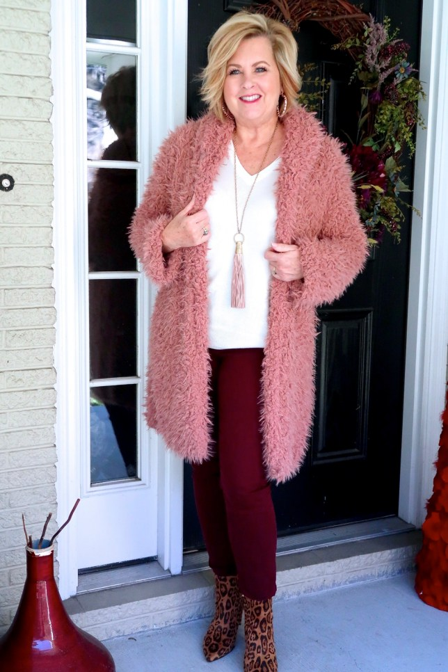 Fashion Blogger 50 Is Not Old is wearing a pink sherpa warm and cozy coat with burgundy pants and ankle boots in animal print