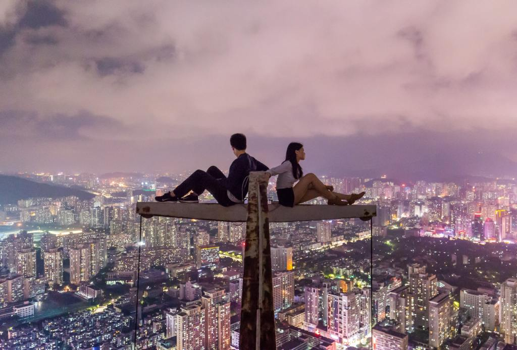 Two people sit on an I beam that has a cross section high up over a city view. they have their back to each other as if being accountable for being there.