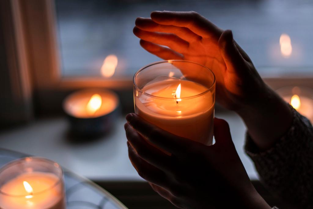 hands holding a lit memorial candle with a candle in the window in the background. The more traditional christian memorial candles