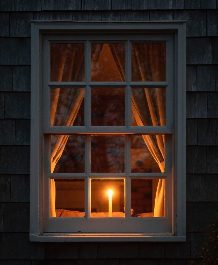 A tall candle lit in a house window, you can see the room inside is dark, the view is from outside looking into the window where a candle is lit