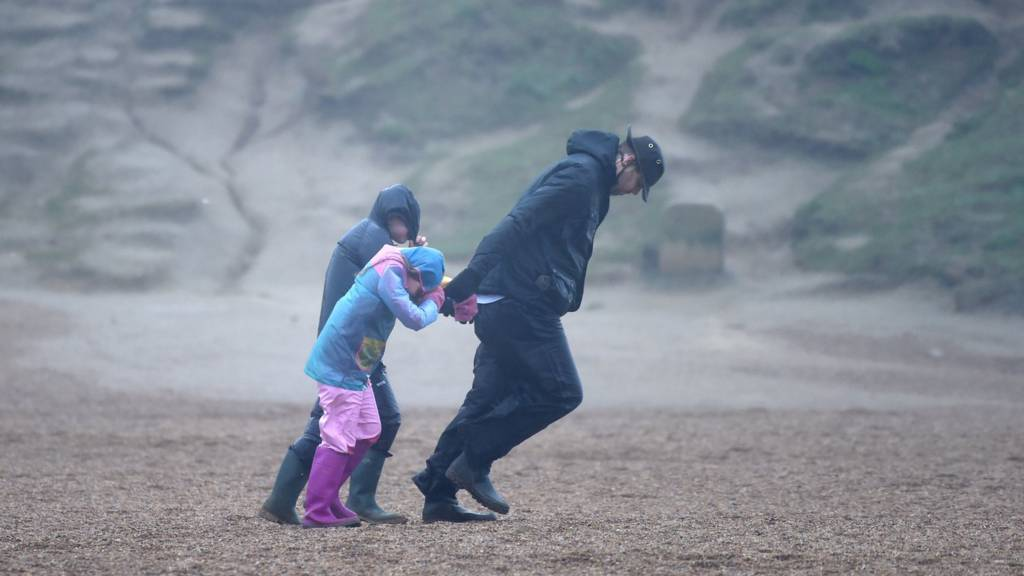A man pulling his children in a storm, the new normal is a struggle but they will get there.