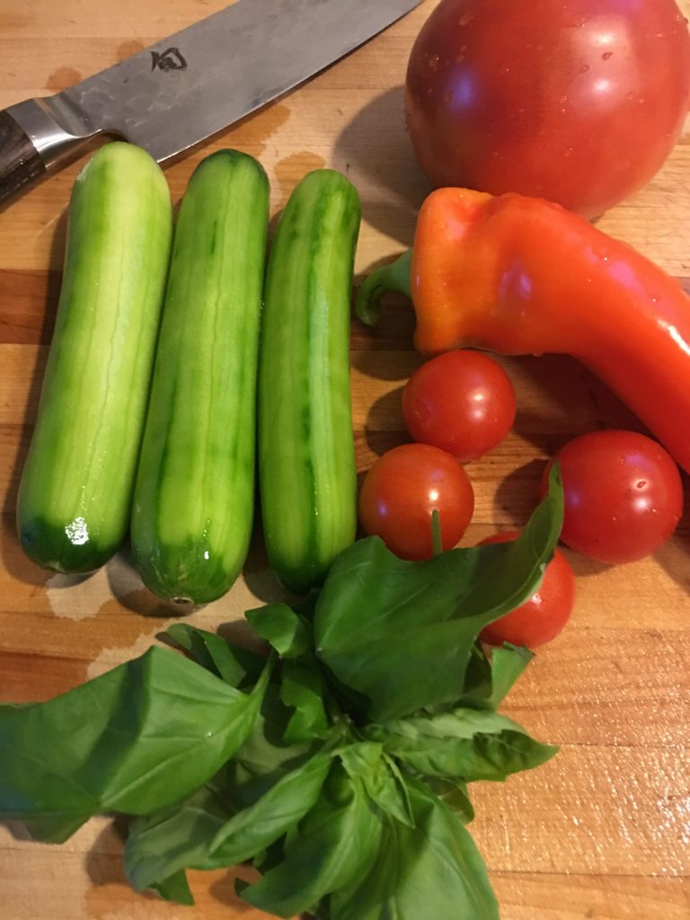Tomoes, cucumbers, basil and a pepper on a chopping board with a knife ready to make salad