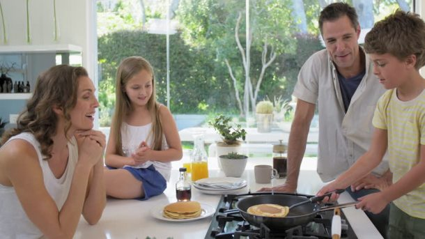 A family makes breakfast together, the little boy is turning pancakes. Eat well-well-blanced meals