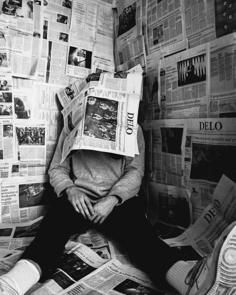 A man sits with newspapers plastered all over the walls, and over his face. he's tired of reading the news about cornavirus