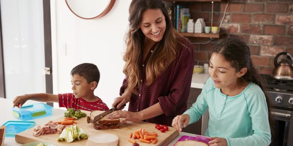 a family cooks together to help out mom who works so much she's tired.