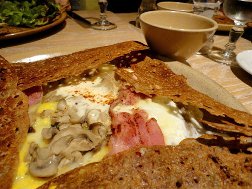a crepe with mushrooms, eggs, cheese and ham. Galette for breakfast on a place with a coffee
