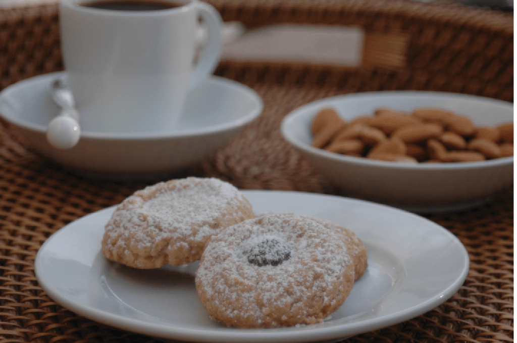 A plate of snow cap almond cookies with an espresso and bowl of almonds on the background.