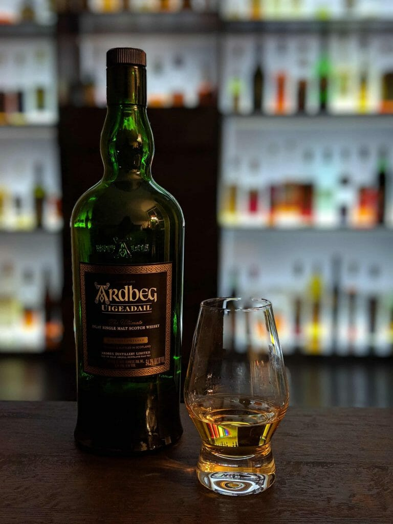 Glass filled with whisky next to dark green bottle in front of backlit bar