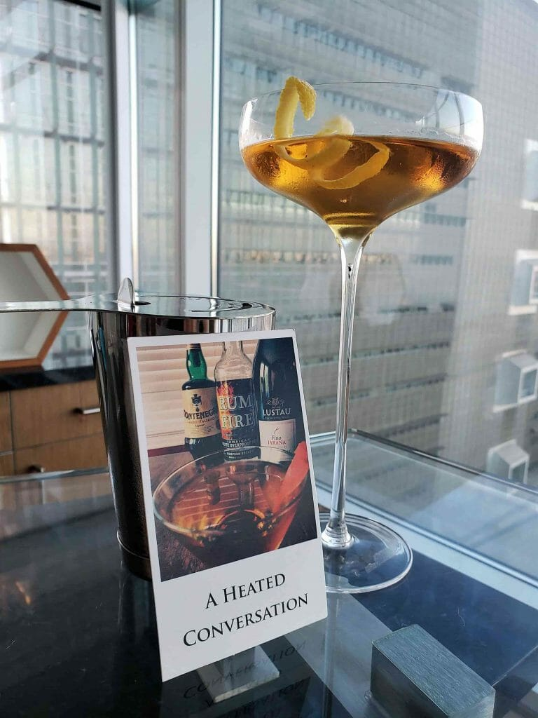Cocktail with long stemmed glass next to book