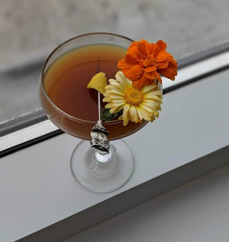 Cocktail with brown whisky and flower garnish with silver toothpick, higher overhead