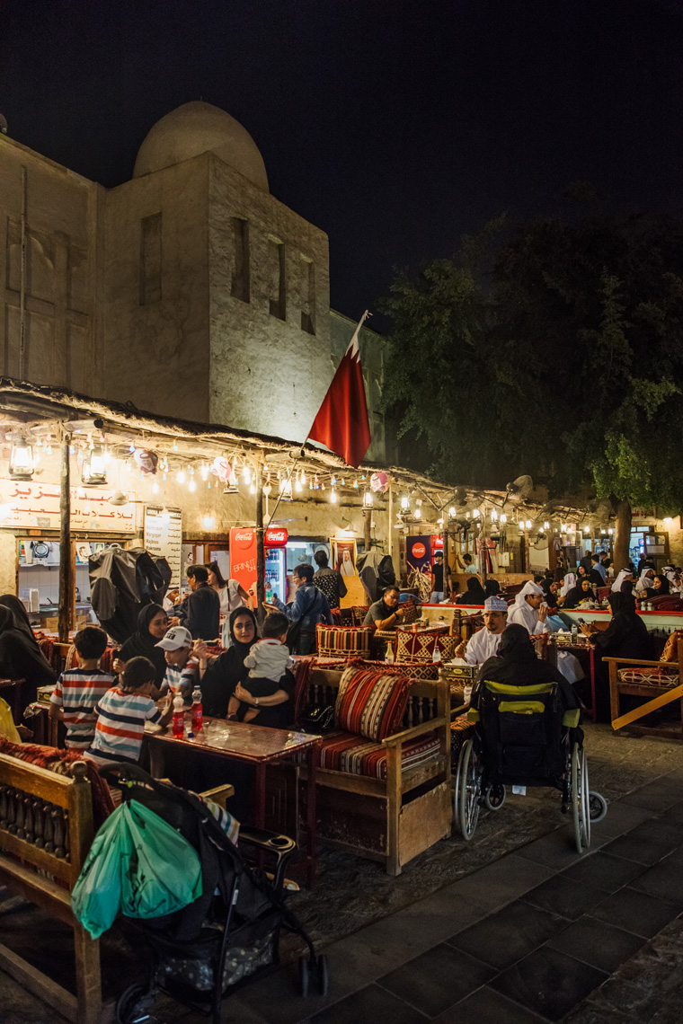 People sitting at tables outside the souq at night