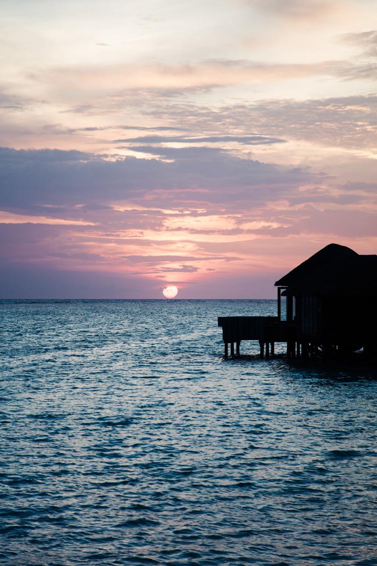 Purple sunset behind overwater villas