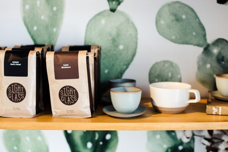 Bags of coffee and mugs on a shelf