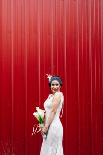 bride posing against red textured wall