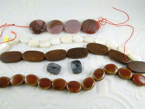 From top to bottom: Agate, shell, wood, larvikite, and glazed ceramic