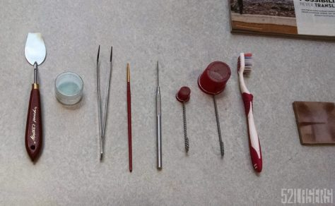 Starting tools, from left to right: Spatula, plastic container (just to keep spatula level), tweezers, fine tipped brush, awl, small sifter, large sifter, toothbrush, foam backed sanding block