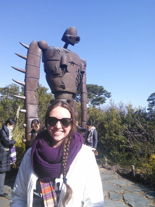 A young woman with sunglasses standing in front of a model of a robot from Castle in the Sky at the Studio Ghibli Museu