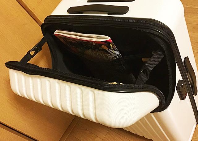 トップオープン型スーツケースのインナーポケットを開いて雑誌を入れた画像