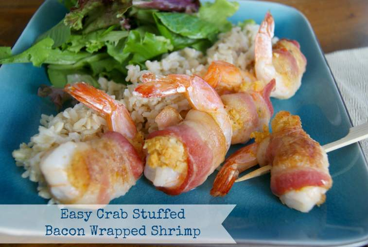Baked crab stuffed shrimp wrapped in bacon, served with brown rice and salad on a blue plate.