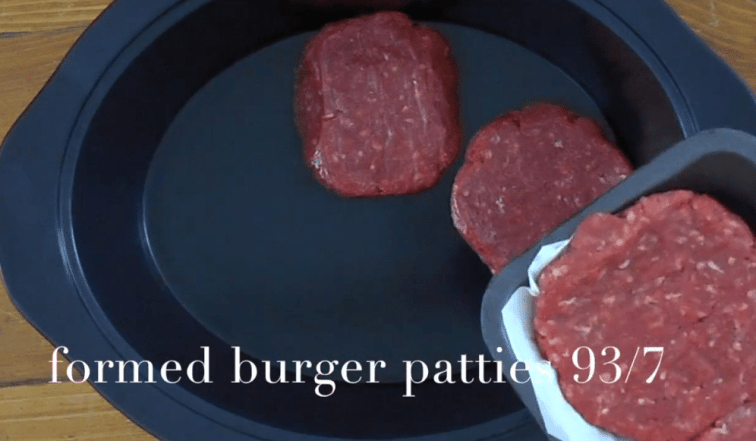 Hamburger patties being placed in a slow cooker