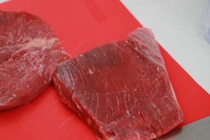 Two cuts of steak on a red colored cutting board.