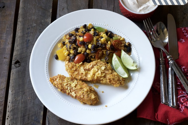 white plate with crispy tortilla chicken strips with black bean and corn dinner garnished with sliced limes.