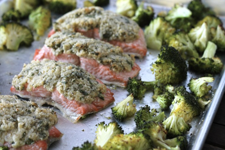 cooked broccoli and salmon topped with mayonnaise, parmesan cheese, almond meal, parsley and lemon, all in one pan silver baking sheet.