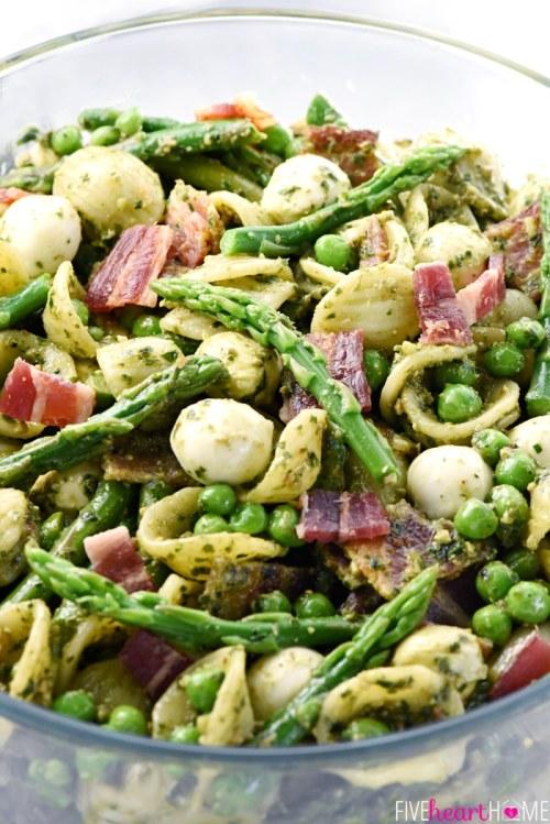 Pasta, bacon, peas, asparagus, mozzarella balls all served in a clear bow.