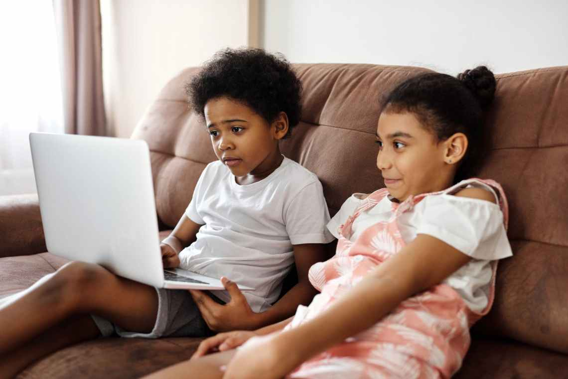 siblings sitting on a couch and looking at a laptop