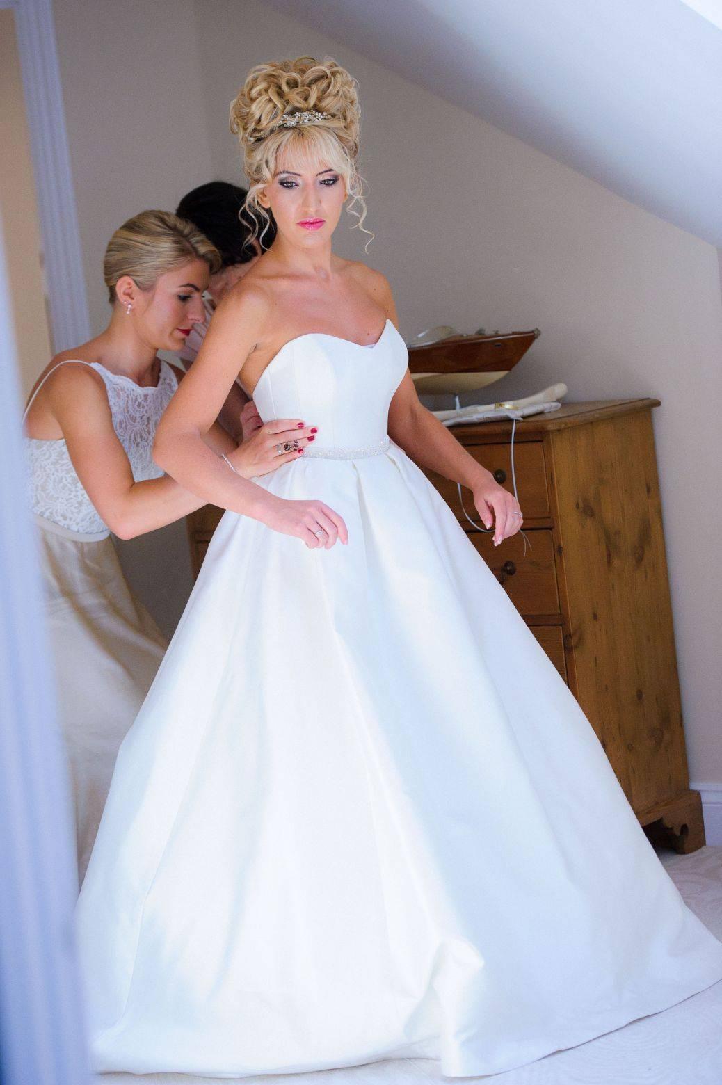 bride getting into dress 1038x1560