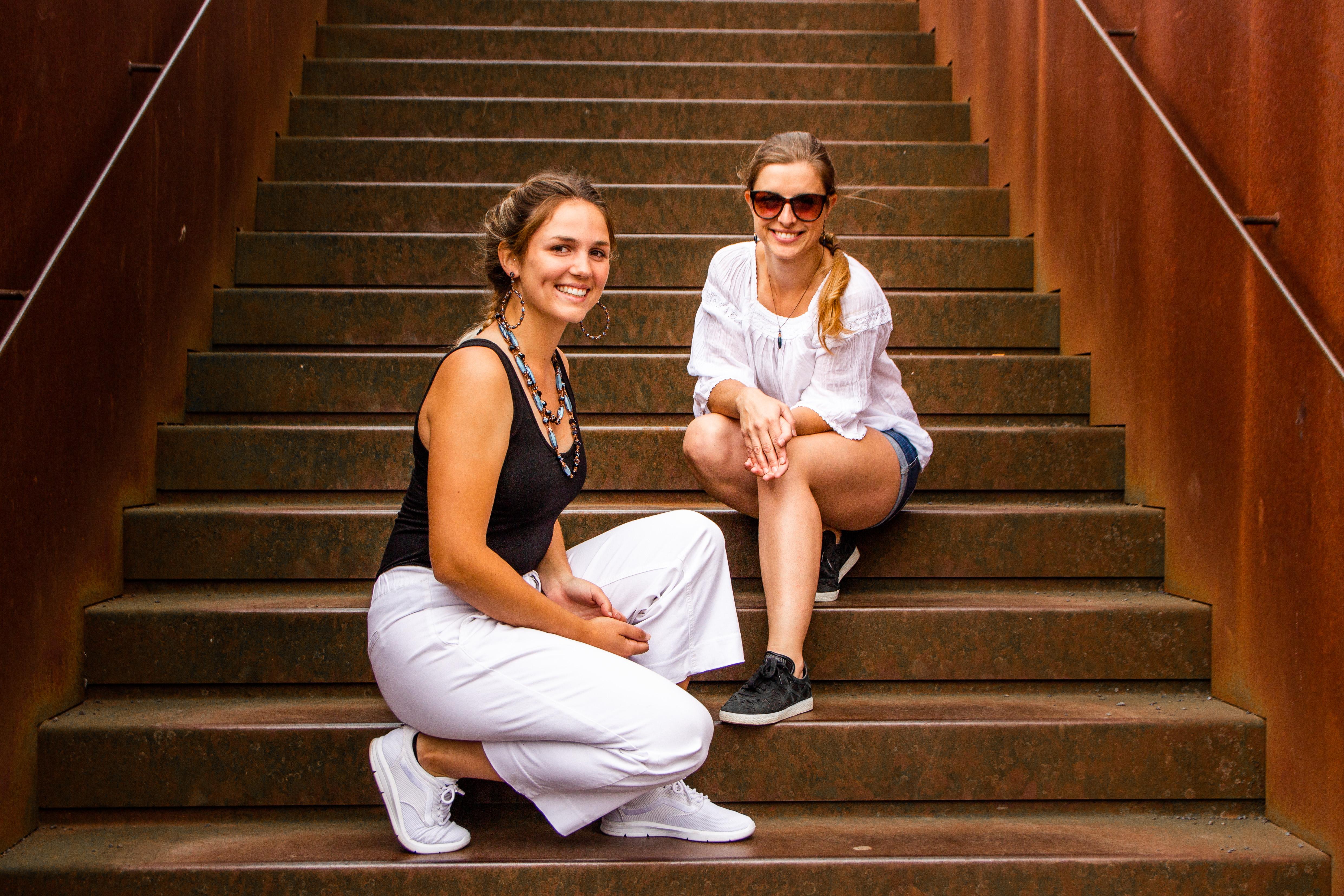 Junge Frauen sitzen mit Ihren Glitzerstücken von Konplott auf einer Treppe