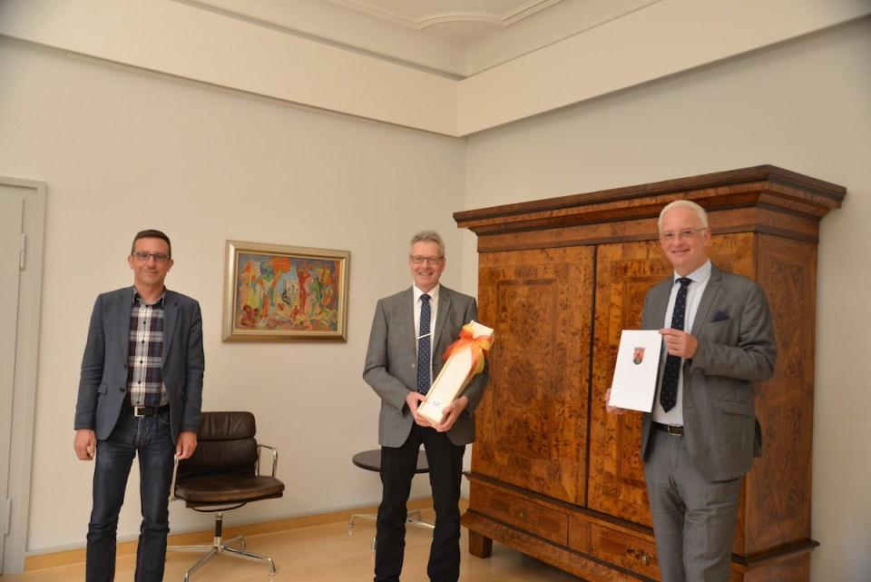 OB Wolfram Leibe (r.) und Dezernent Thomas Schmitt (l.) gratulieren Professor Michael Embach zum 40-jährigen Dienstjubiläum. Foto: Presseamt Trier