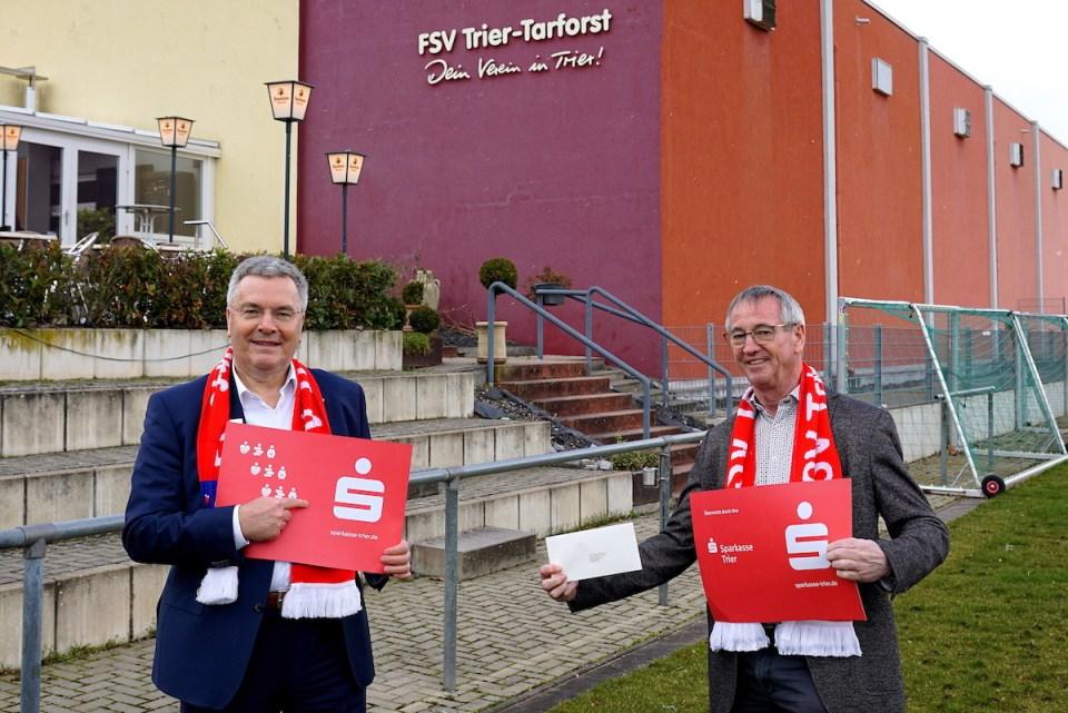 Das Foto zeigt den Vereinsvorsitzenden Werner Gorges (rechts) und Wolfgang Ziewers von der Sparkasse Trier (links) bei der Spendenübergabe vor dem Sportzentrum