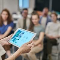 Das Bild zeigt ein Tablet vor Seminarteilnehmenden. Foto: fauxels von pexels