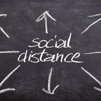"""Das Bild zeigt ein Kreietafel mit Pfeilen und dem Wort """"Social Distance"""". Foto: Bild von Gerd Altmann auf Pixabay"""