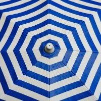 Das Bild zeigt einen blau weiß gestreiften Sonnenschirm von oben. Foto: Free-Photos auf Pixabay