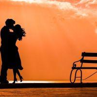 Das Bild zeigt ein Liebespaar neben einer Bank im Sonnenuntergang am See. Bild von Dimitris Vetsikas auf Pixabay