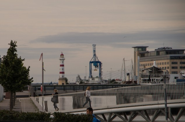 Streetscene with a view on Malmö harbour with cranes and the lighthouse.
