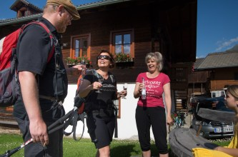 Two women and a man drink on a sunny day outside a wooden house in Lerch, Austria
