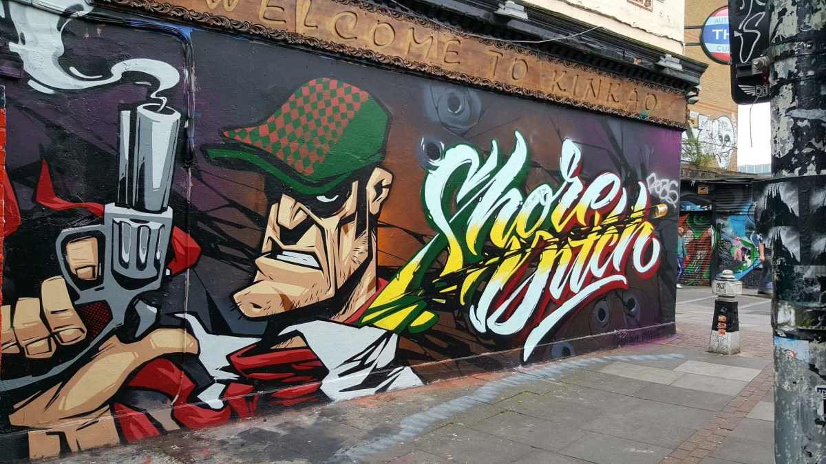 Streetart in Shoreditch, London, showing a gangster with a smoking gun