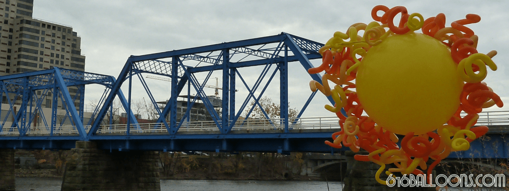 Giant 3' yellow balloon sun and the awesome Blue Grand Rapids and Indiana Railroad Bridge in the background. Built in 1892, it is among longest truss bridges in Michigan. It is now a pedestrian bridge. 616Balloons.com Grand Rapids, Michigan. Specializing in high end balloon art & decor for the best corporate or private parties and events in West Michigan.