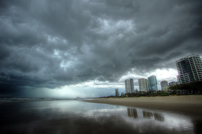 Beach with city scape in background and dark clouds overhead