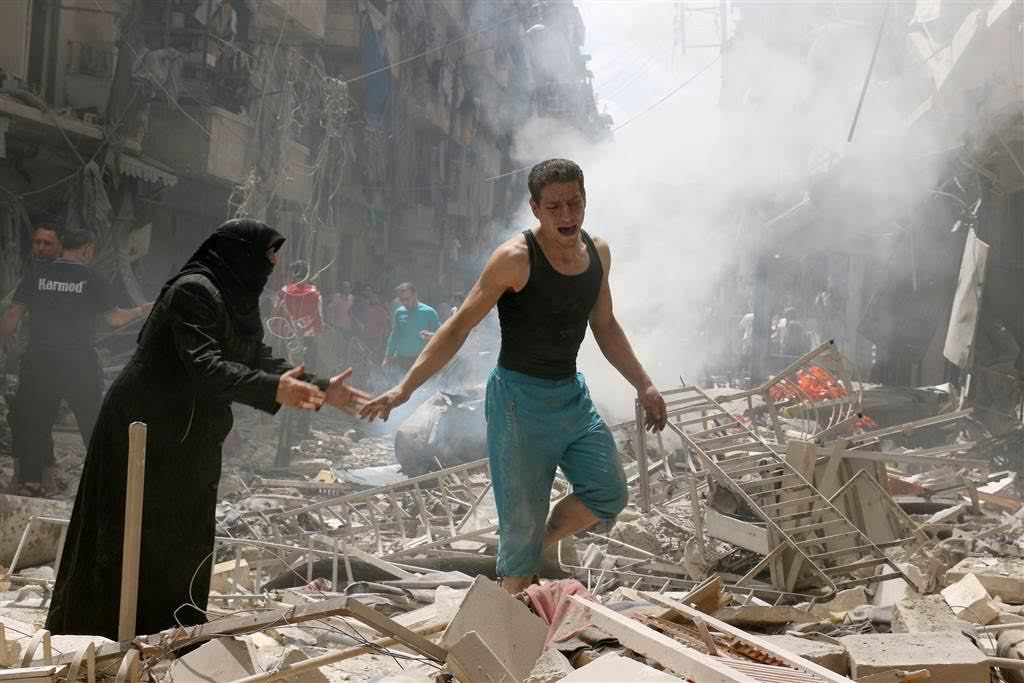P eople walk through the rubble of destroyed buildings following a reported air strike on the rebel-held neighborhood of al-Kalasa in Aleppo AMEER ALHALBI