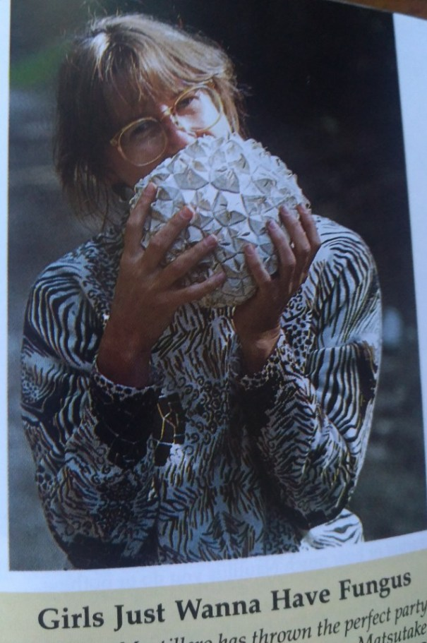 A woman with glasses, holding a large mushroom that obscures the bottom half of her face.