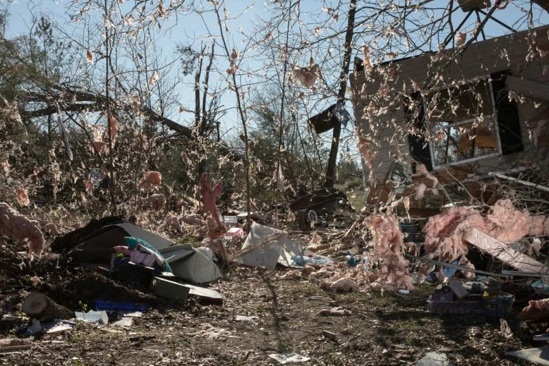 Изоляция от дома была разбросана на деревьях после того, как торнадо прошел через область, убив 23 человека и разрушив дома, в Борегарде, штат Алабама, 4 марта.
