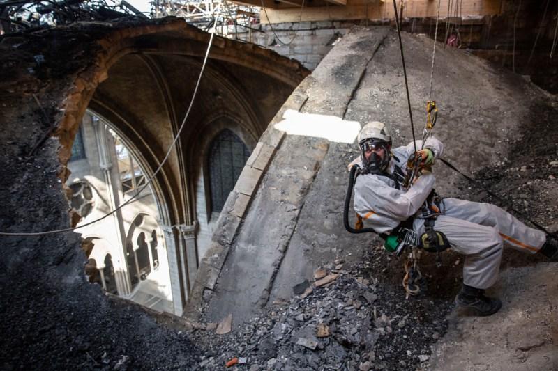 25 июня техник возле открытой части крыши Нотр-Дама в Париже. После апрельского пожара некоторые части собора с тех пор подвергались ливням и высоким температурам.