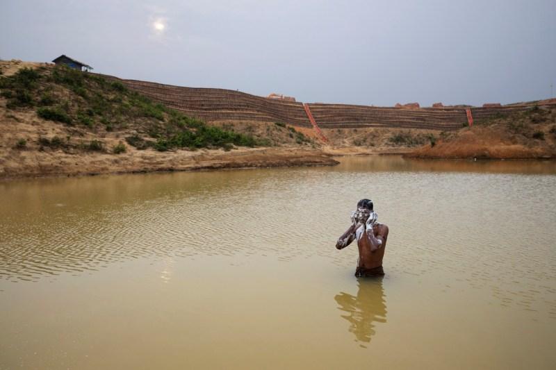 Мужчина-рохингья купается в искусственном пруду возле лагеря, где он живет. За ним идет строительство удлинения лагеря 20.