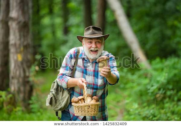 Old bearded man presenting a mushroom from his basket and smiling.