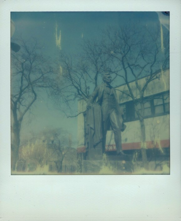 An Polaroid-style instant photograph depicting the statue of Abraham Lincoln in Chicago's Lincoln Square neighborhood.