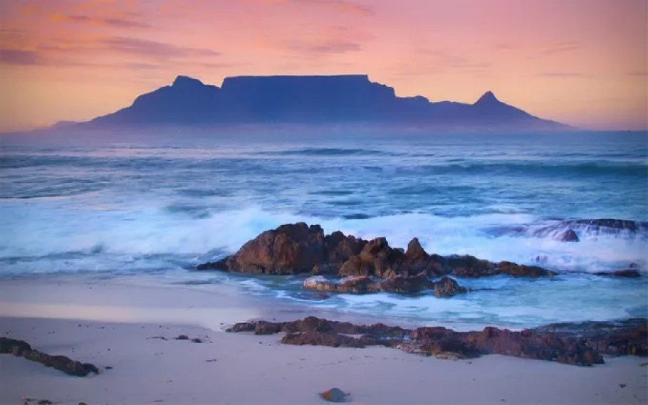 Sunset behind the ocean and Table Mountain in Cape Town